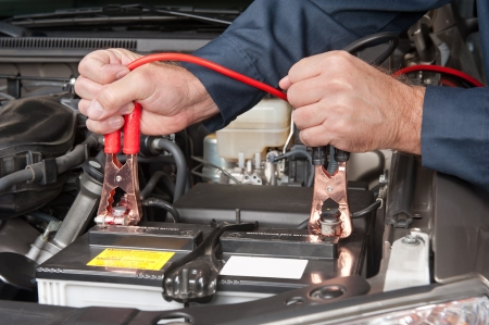 cables: A car mechanic uses battery jumper cables to charge a dead battery.