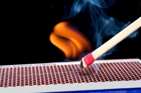 A matchstick lights after it is struck agains the flint surface of a match box.