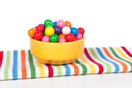 A bowl of colorful gumballs on a vibrant napkin. Фото со стока