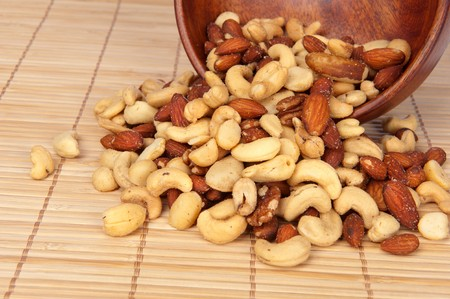 A spilled wooden bowl of mixed nute including almonds, cashews, hazelnute and walnuts. Stock Photo