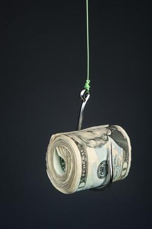 Un rollo de dinero en efectivo en un fishook con un telón de fondo degradado gris oscuro.  Foto de archivo