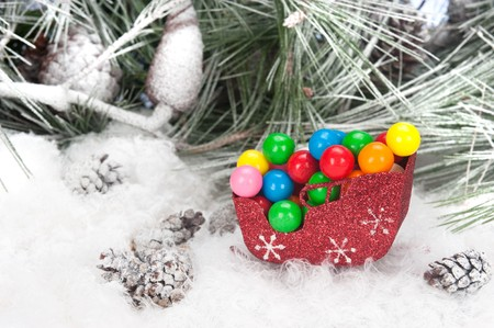 Studio shot setting of a Christmas sleigh filled with colorful holiday gumballs set in a snowy, pine tree background. photo