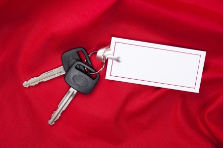 car keys: A set of new car keys with ribbon attached to a blank card for copy.  Good for Valentines Day or Christmas inferences or any inference where red is the designers appeal.