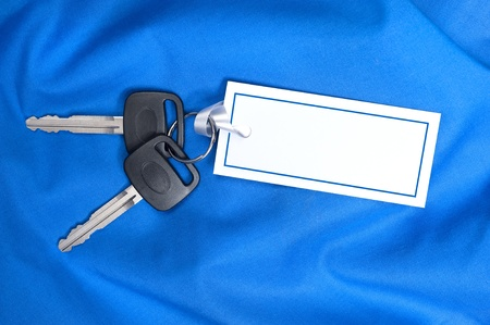 inferences: A set of new car keys with ribbon attached to a blank card for copy.  Good for Valentines Day or Christmas inferences or any inference where blue is the designers appeal. Stock Photo