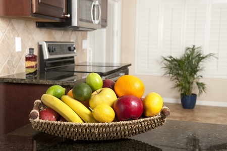 A fresh fruit basket on a granite countertop in a newly remodeled kitchen. Stock Photo