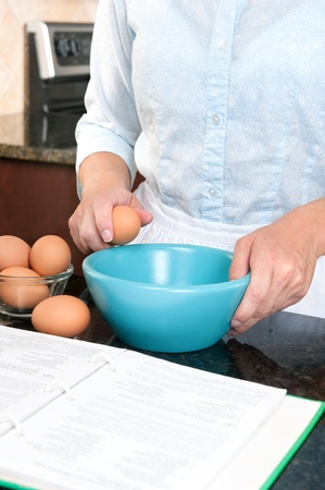 A homemaker cracks an egg into a mixing bowl while following the instructions of a cookbook. Stock Photo - 8430365