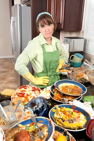 A homemaker get ready to wash dishes with little enthusiasm. photo