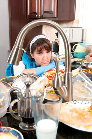 messy kitchen: A homemaker gets ready to wash dishes with little enthusiasm. Stock Photo