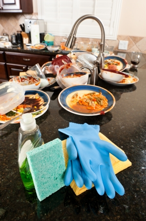 Kitchen and dish washing cleaning supplies ready to be used on dirty, filthy dishware. photo