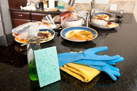messy: Kitchen and dish washing cleaning supplies ready to be used on dirty, filthy dishware.