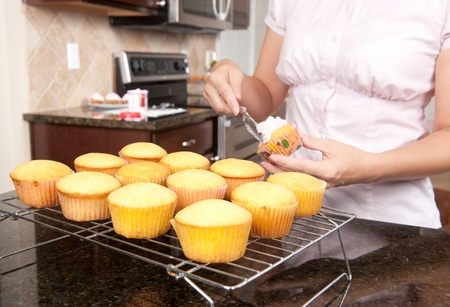 A woman spreads icing over a cupcake before starting on a new batch.  Focus is on middle row of cupcakes. Stock Photo - 8430370