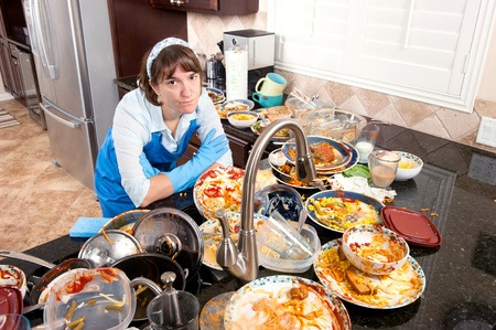 manos sucias: Una mujer que llevaba guantes de lavado de plato y un delantal contempla haciendo los platos.