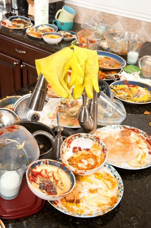 A pair of yellow dish washing gloves hangs on a sink faucet surrounded by filtyh dishes.