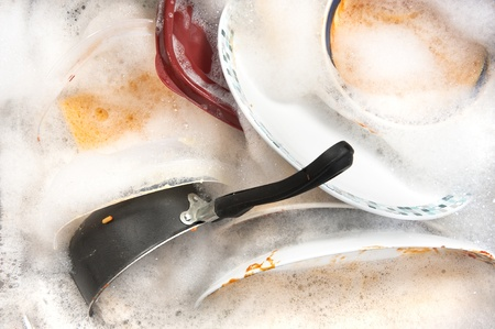 A sink full of dirty dishes and soapy water.