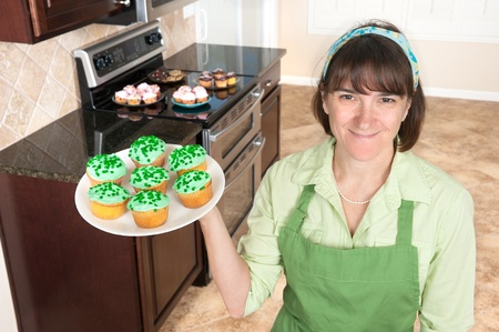 homemaker: A homemaker displays a set of green cupcakes with clover sprinkles in her kitchen.