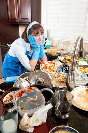 A frustrated woman prepares to wash a large set of dirty dishes. Banque d'images