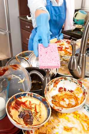 A homemaker offeres her dish sponge to help wash dishes Stockfoto