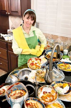 A smiling homemaker gets ready to wash a mass of filthy dishes. Stock Photo - 8629688