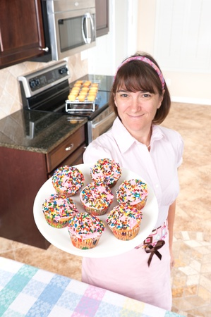 homemaker: A homemaker shows off her decorated cupcakes with pink icing and candy sprinkles.  Focus is on the cupcakes.