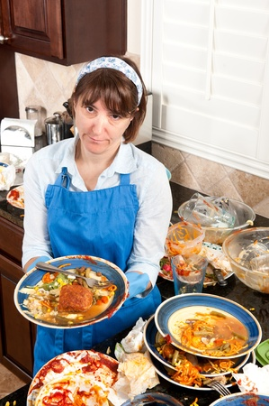 mess: A homemaker gets ready to wash dishes with little enthusiasm. Stock Photo