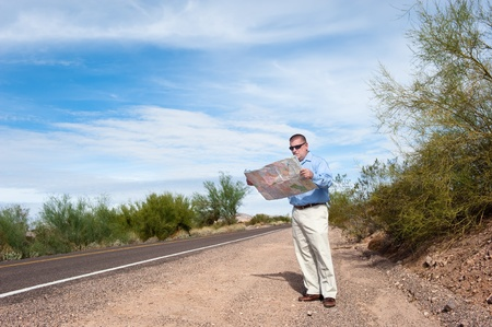 roadmap: A lost man stands alone on a deserted road reading a map.