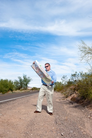 A man stands along a deserted road reading a roadmap photo