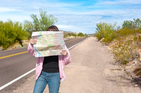 A woman stands along side a remote deserted road reading a map. Banco de Imagens