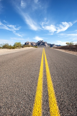 vertical divider: A long empty road in a remote desert location leaves a diminishing perspective.