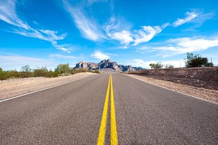 Een afgelegen en verlaten woestijn weg met een beautifyl hemel.  Stockfoto