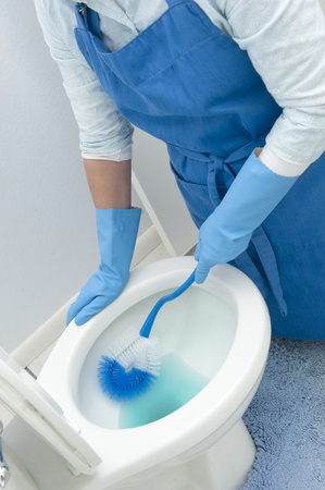 clean up: A woman cleans a bathroom toilet with a scrub brush.