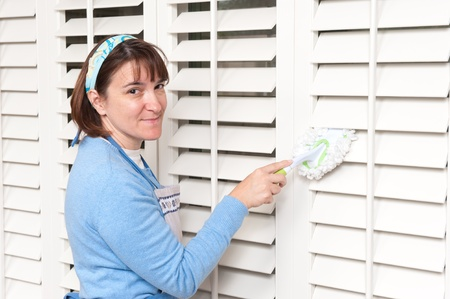 A homemaker uses a hand held duster to clean some wooden window shutters Stock Photo - 8622450