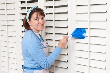 duster: A woman uses a feather duster to clean shutters.
