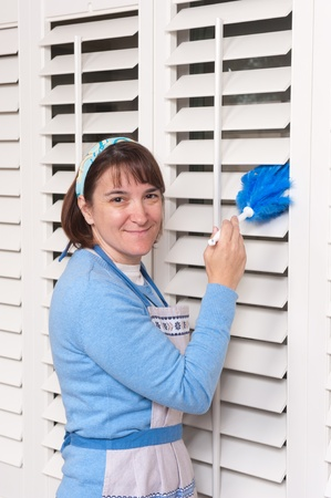 A woman dusting her dirty window shutters. Stock Photo - 8622485