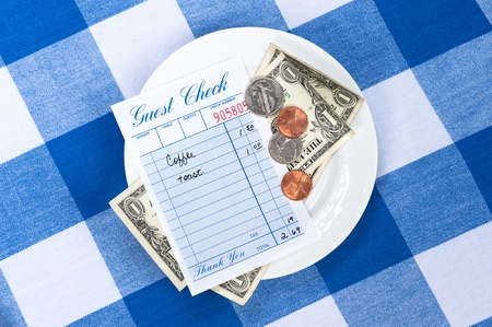 A dining check on a saucer with change from a meal payment.