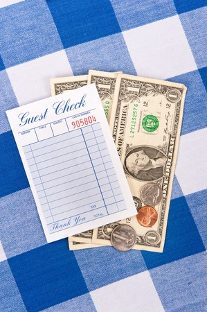 A meal check from a restaurant with change on a checkered table cloth photo