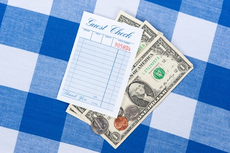 communicated: A meal check from a restaurant with change on a checkered table cloth