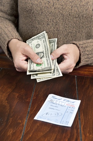 A woman pays her meal bill with cash. photo