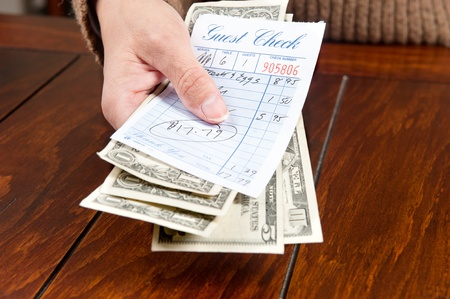 cash receipt: A woman pays her meal bill with cash.