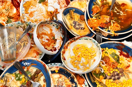 messy: A mass of dirty, filthy dishes with food scraps waiting to be washed.