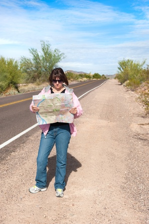 A woman stands along side a remote deserted road reading a map. photo