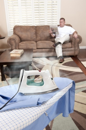 A man sit on his couch while the iron burns and scorches his dress shirt. photo