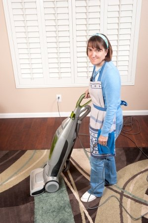 A woman is conducting housework by vacuuming a rug on a wooden floor. photo