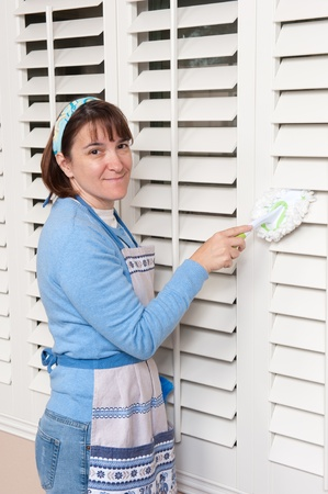 A woman dusts her window shutters while cleaning the house Stock Photo - 8688515
