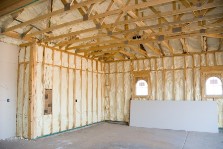 tablaroca: Una habitaci�n en una casa reci�n construida es rociada con l�quido aislante de espuma antes de agrega el cart�n de yeso.  Ideal para publicidad de construcci�n de casas nuevas y otras deducciones promocional de construcci�n de casas.