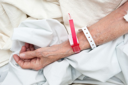 id: An elderly woman wearing medical arm bands for indentification purposes. Stock Photo