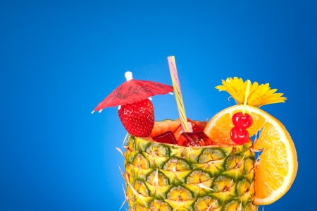 A cold, refreshing tropical rum drink with a pineapple glass, strawberry, cherries and an orange slice shot against a blue gradient. Stock Photo - 8884063