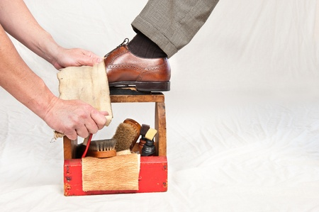 polish: A man gets his shoes polished by a worker using a vintage shoe shine box with camel hair brushes, polishing rag, polish and a wooden shoe platform.