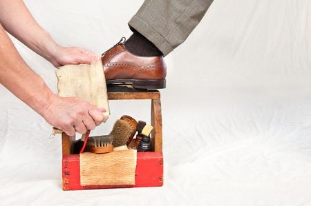 shoe boxes: Un hombre obtiene sus zapatos pulidos por un trabajador mediante un cuadro de brillo de la cosecha de zapato con pinceles de pelo de camello, pulido de trapo, polaco y una plataforma de madera de zapato. Foto de archivo