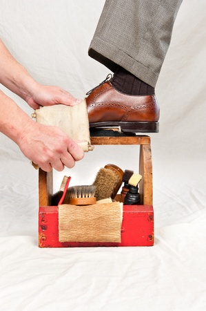 A man gets his shoes polished by a worker using a vintage shoe shine box with camel hair brushes, polishing rag, polish and a wooden shoe platform. photo
