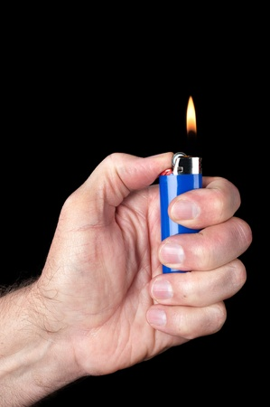 hand held: Image of a person lighting a blue portable butane lighter against a dark background.  Image good for smoking, mechanical or dexterity inferences. Stock Photo